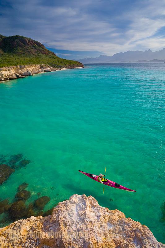 Sea kayaker paddling below cliff on Isla Carmen, Sea of Cortez, Baja, Mexico.