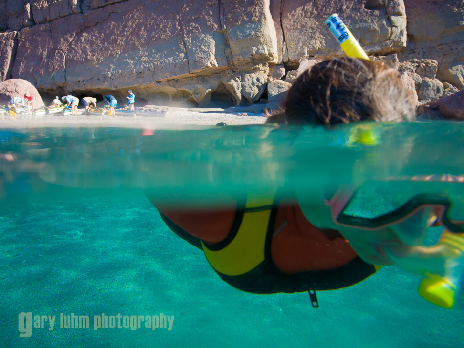 Snorkling out from shore, sea kayakers on the beach. Isla Carmen, Sea of Cortez, Baja, Mexico.