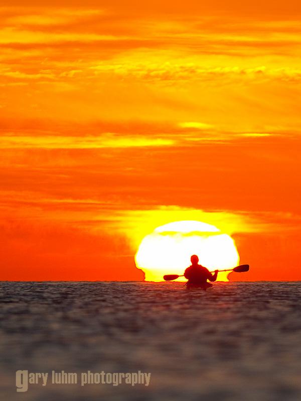 Sea kayaker paddles toward sunrise, Sea of Cortez, Baja, Mexico.