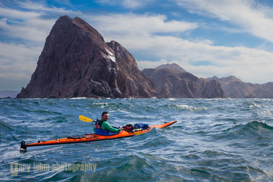 Sea kayaker in refracted waves off Punta Lobos, Isla Carmen, Baja, MX.
