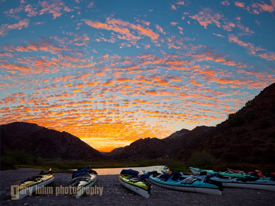 Sea kayaks on the shore at Puerto Balandra on Isla Carmen at a classic Baja sunrise.