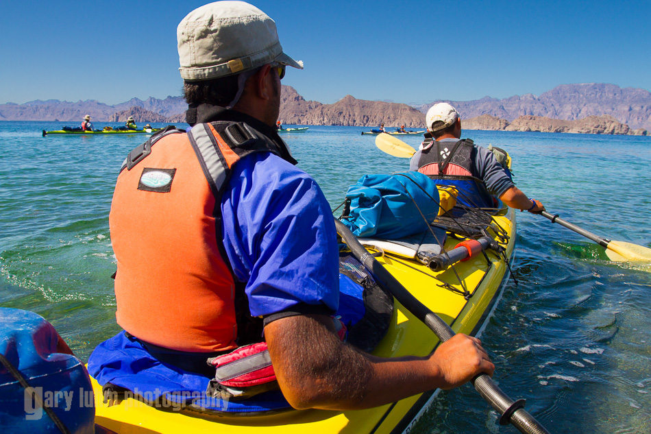 Sea kayak guides launch a double kayak from Punta Arena on Isla Carmen, Sea of Cortez, Baja, Mexico. (MR)