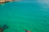 Sea kayaker paddling below cliff on Isla Carmen, Sea of Cortez, Baja, Mexico.