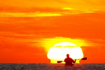 Sea kayaker paddles toward sunrise, Sea of Cortez, Baja, Mexico.