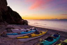 Sunrise with sea kayaks on beach on Isla Carmen, Baja, Mexico.