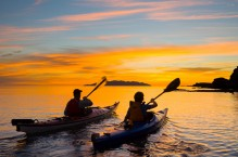 Sea kayakers paddle toward sunrise, Los Gatos, Sea of Cortez, Baja, Mexico.