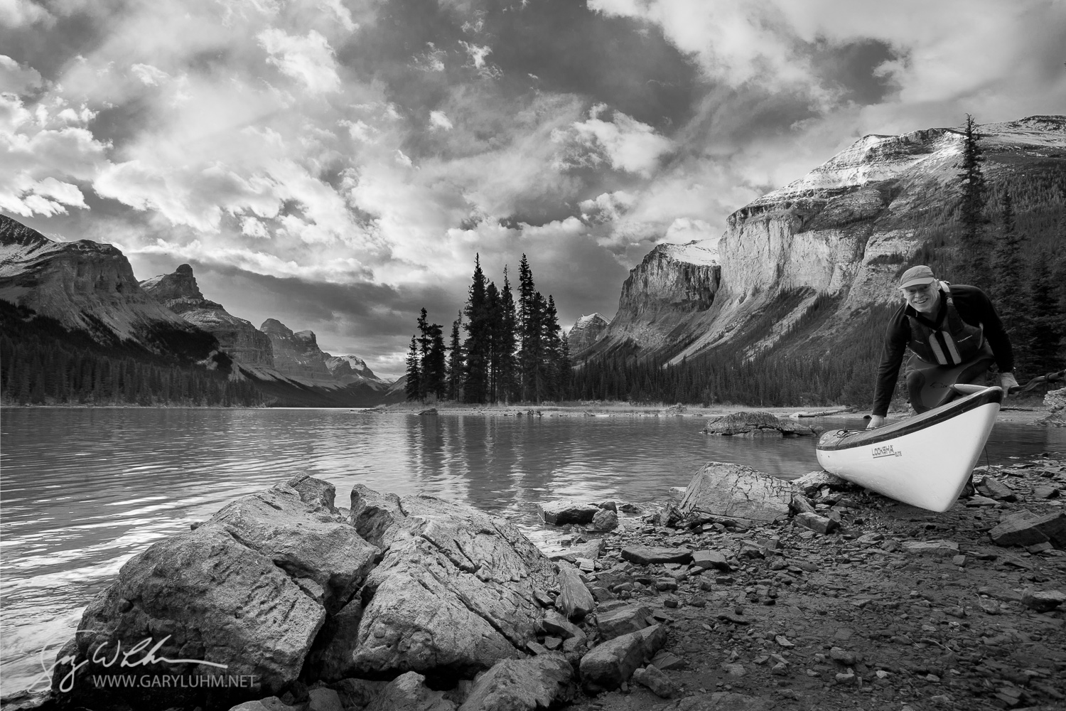 A male sea kayaker brings a kayak ashore at Spirit Island, Maligne Lake, Jasper National Park.