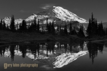 Mt. Rainier reflecting in a tarn. With the sky a plain blue, I reduced it by going less wide. In post I increased the contrast between the warm, sunlit mountain and the bluer trees and sky.