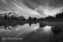 The red sunset may be stunning, but in black and white the dramatic, contrasty sky, the steping-stone rocks, and perfect punctuating firs play a great hamony to a compelling Mt. Rainier. Mt. Rainier National Park.