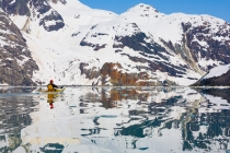 Sea Kayaker paddles toward kayak motherhip Home Shore in John Hopkins Inlet, Glacier Bay National Park, Alaska, USA.