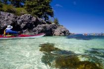 Kayaking glides over white shell beach near Balaclava Island, Queen Charlotte Strait, BC, Canada.