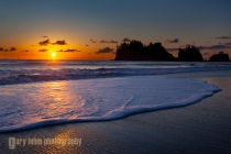 A wave rolls up the beach at sunset at La Push on the Olympic Coast.