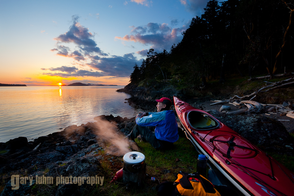 Male sea kayaker enjoying hot tea and sunset while camping on Jones Island, San Juan Islands, Washington State (MR).