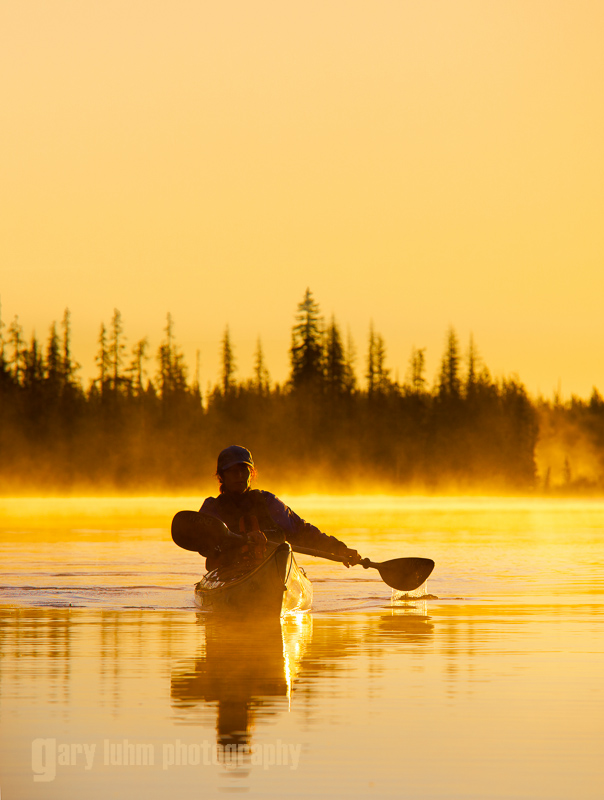 A woman in a sea kayak paddles at dawn on Big Lake, Oregon.