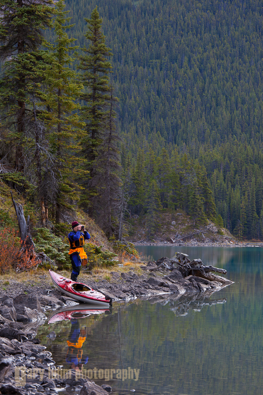 Male kayaker looking through binoculars while ashore on Maligne Lake, Jasper National Park, Alberta.