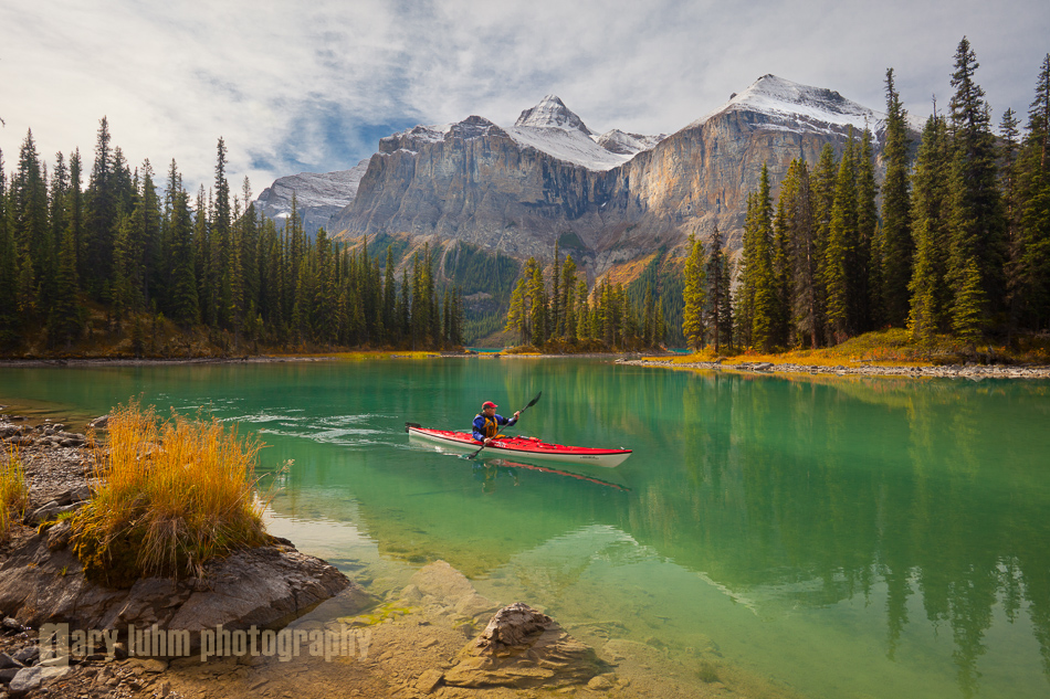 A male sea kayaker paddles on Maligne Lake, Jasper National Park, Alberta.