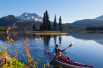 Woman kayaker paddles on Sparks Lake, Oregon, with red columbine in foreground and South Sister behind (MR).
