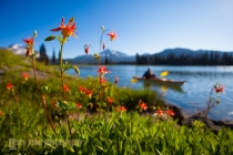 Woman kayaker, South Sister, Broken Top and red columbine on Sparks Lake, Oregon. (MR).