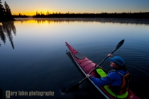 Woman sea kayaker on BIg Lake, Oregon at sunrise.