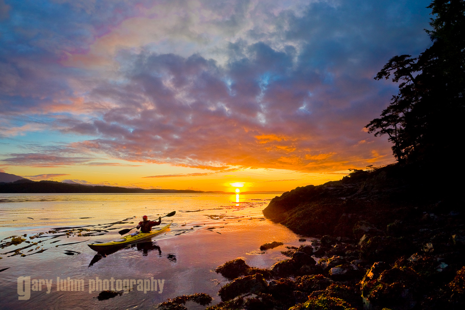 Man paddling sea kayak at sunset in Blackfish Sound near Telegraph Cove, Vancouver Island, BC, Canada.