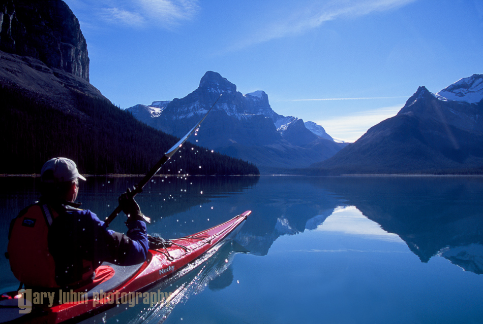 Sea kayaker on flat water morning, Maligne Lake, Alberta, Canada.