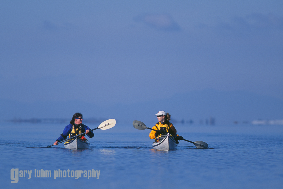 Women sea kayakers on a blissful day, Port Susan, Puget Sound, Washington, USA.