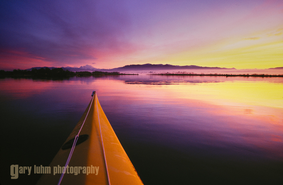 Kayak bow and sunrise on Skagit Bay, Washinton, USA.
