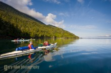 Sea kayakers underway along the Vancouver Island shore. Johnstone Strait, British Columbia, Canada. (MR)