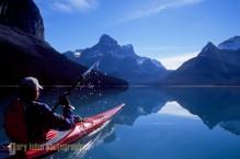 Sea kayaker on flat water morning, Maligne Lake, Alberta, Canada.