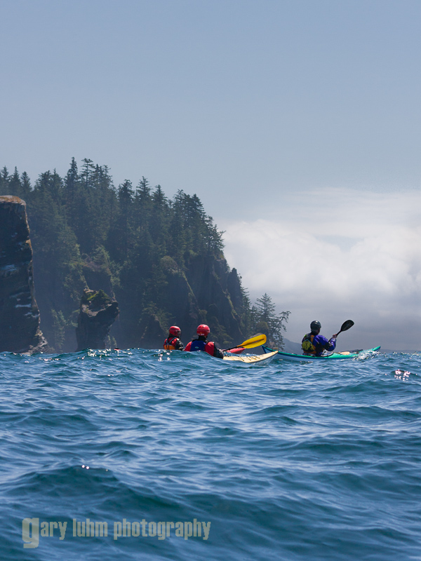 Sea kayakers approach moody storm at Cape Flattery, Washington State.