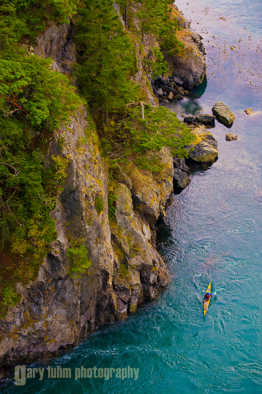 Aerial view of sea kayaker in swirling tidal current at Deception Pass, Washington State. (MR).