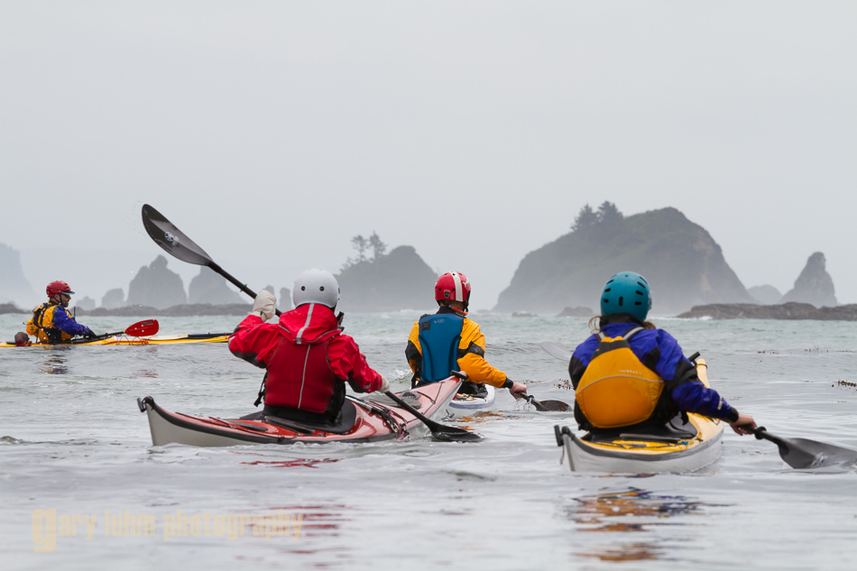 Sea kayakers navigate ocean swell and sea stacks along the Olympic coast, Graveyard of the Giants, Olympic National Park, Washington State.