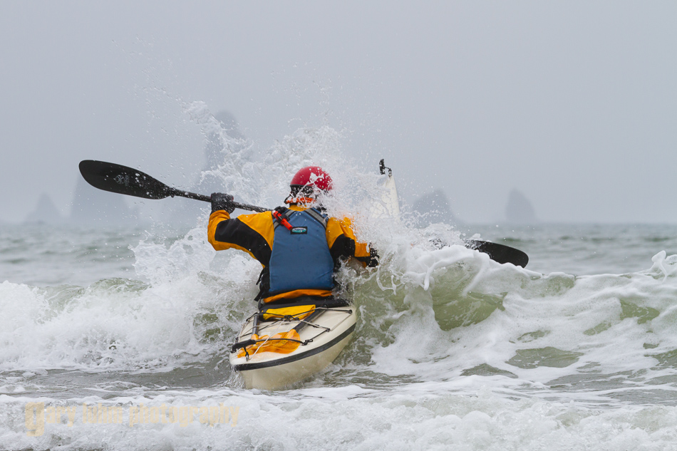 Sea kayaker Alan Marshall busts through mild surf at Third Beach, Olympic National Park, Washington State.