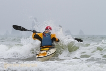 Sea kayaker Alan Marshall busts through mild surf at Third Beach, Olympic National Park, Washington State.