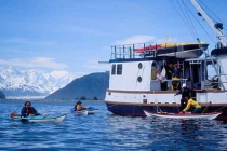 Launching sea kayaks. Launching sea kayaks from the mothership in Taylor Bay, below the Fairweather Range, Glacier Bay National Park.