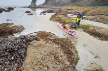 Sea kayaker packing kayak in intertidal at Point-of-Arches, Olympic National Park, Washington State.