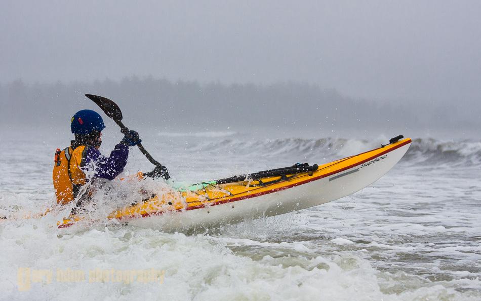 Sea kayaker launching from Makah Bay, Olympic Coast, Washington State.