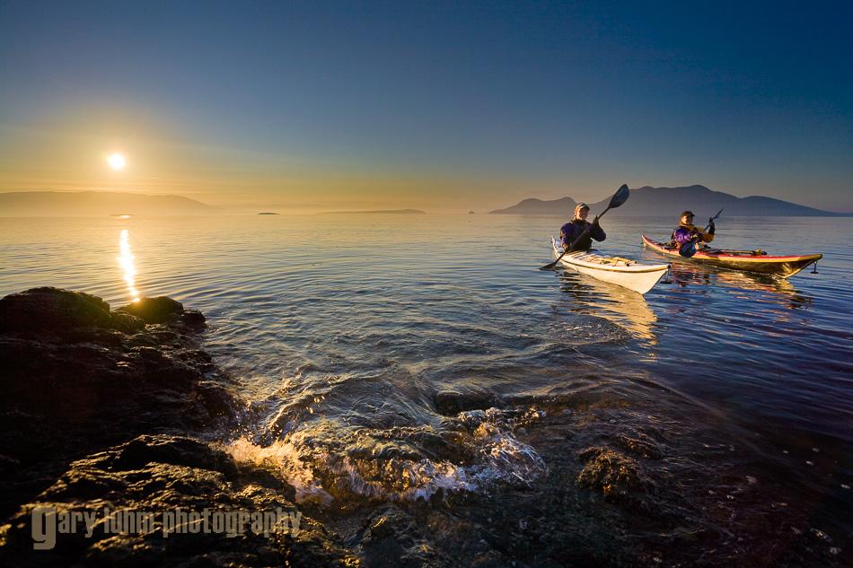 Two women sea kayakers paddling at dawn at Doe Island, San Juan Islands, Washington State.(MR)