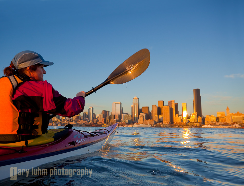 Woman sea kayaker paddling toward downtown Seattle at sunset, Elliott Bay, Washington State.