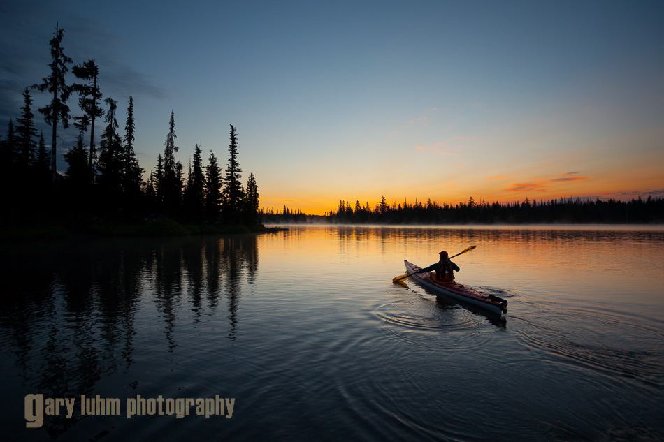 Sea kayaker on Big Lake at dawn, Oregon Cascades.