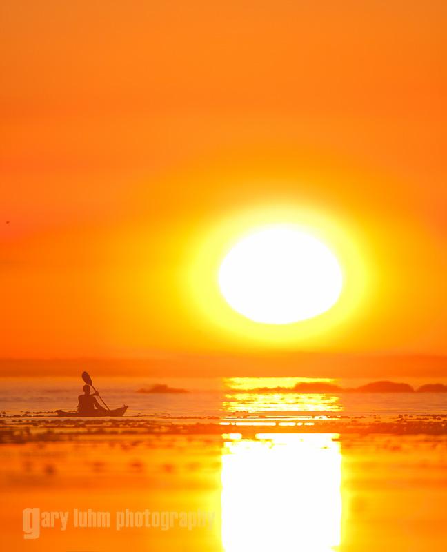 Sea kayaker paddling into big sun sunset, Toleak Point, Olympic National Park, Washington State.