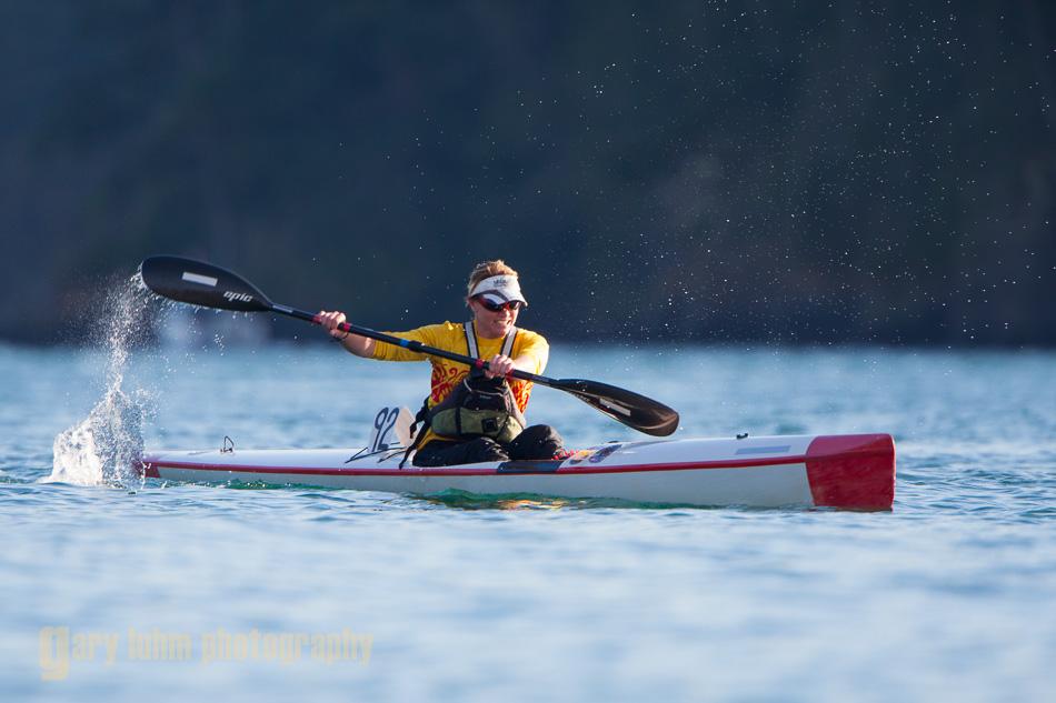 Woman kayaker races her high-performance surf ski kayak at Deception Pass, Washington State.