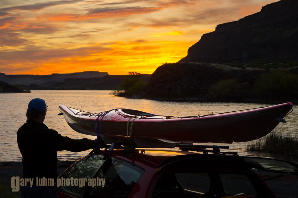 Man unloading sea kayak from car at dawn, Alkili Lake, Washington State