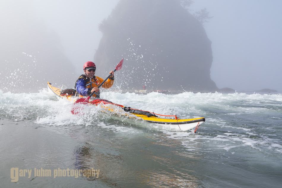 Sea kayaker launches through mild surf at Point of Arches, Olympic National Park, Washington State.