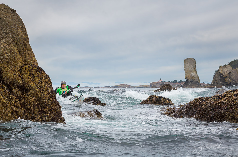 Sea kayaker Leslie Mix in rock garden in moderate swell, near Cape Flattery on the Olympic Coast, with Tatoosh Island lightouse and the Juan de Fuca Pillar behind.