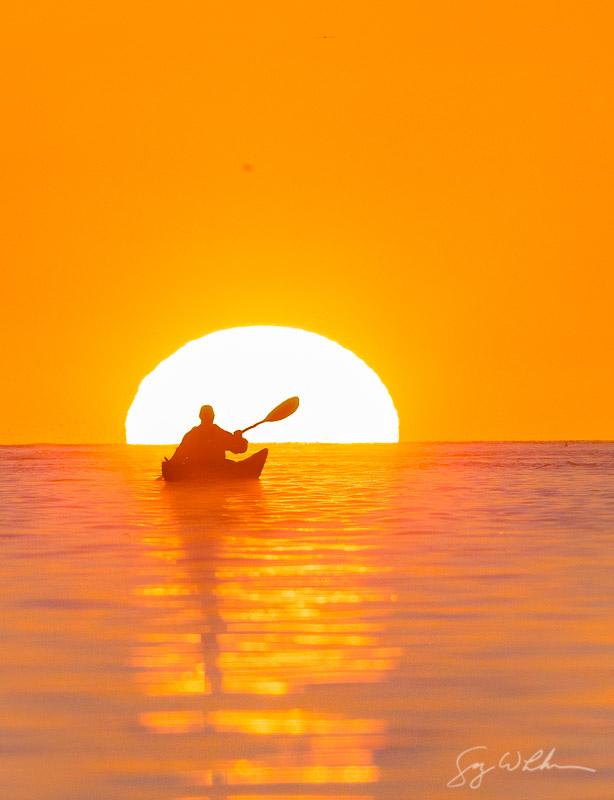 Woman sea kayaker insde the ball off the setting sun, paddles near the Deception Pass Bridge.