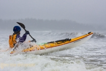 Sea kayaker launching from Makah Bay, Olympic Coast, Washington State.