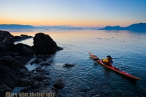 Woman sea kayaker paddling at dawn at Doe Island, San Juan Islands, Washington State.(MR)