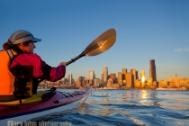Woman sea kayaker paddling toward downtown Seattle at sunset, Elliott Bay, Washington State.