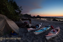 Sea kayaks and tent at kayaker camp, with crescent moon at sunset, at Toleak Point on the Olympic Coast, Olympic National Park, Washington State.